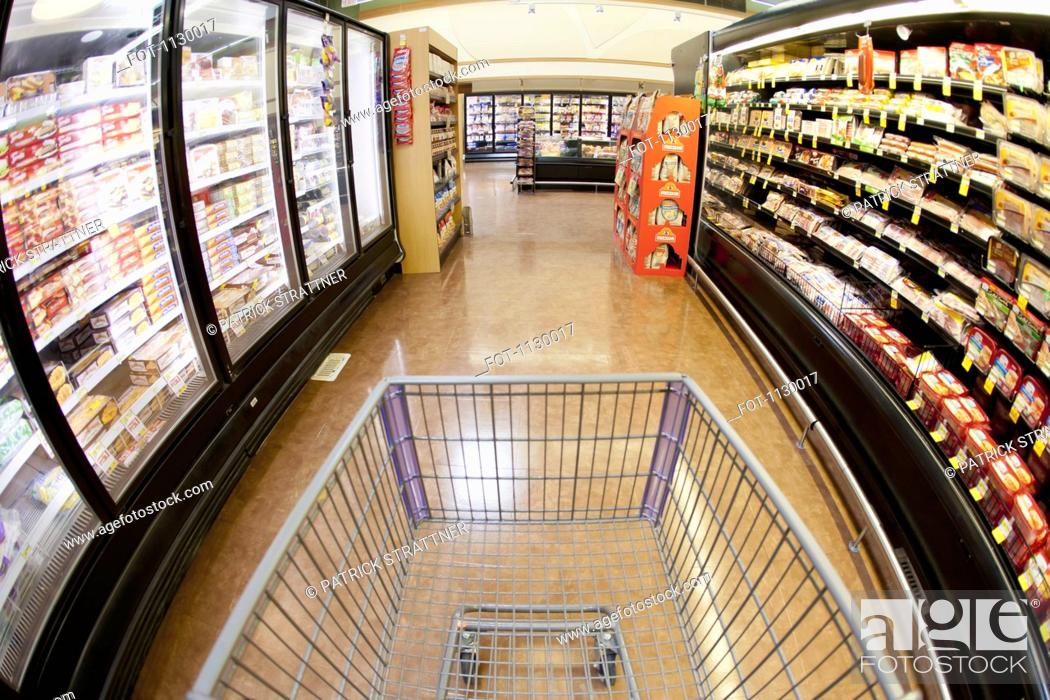 Stock Photo: A shopping cart on an aisle in a supermarket, personal perspective.