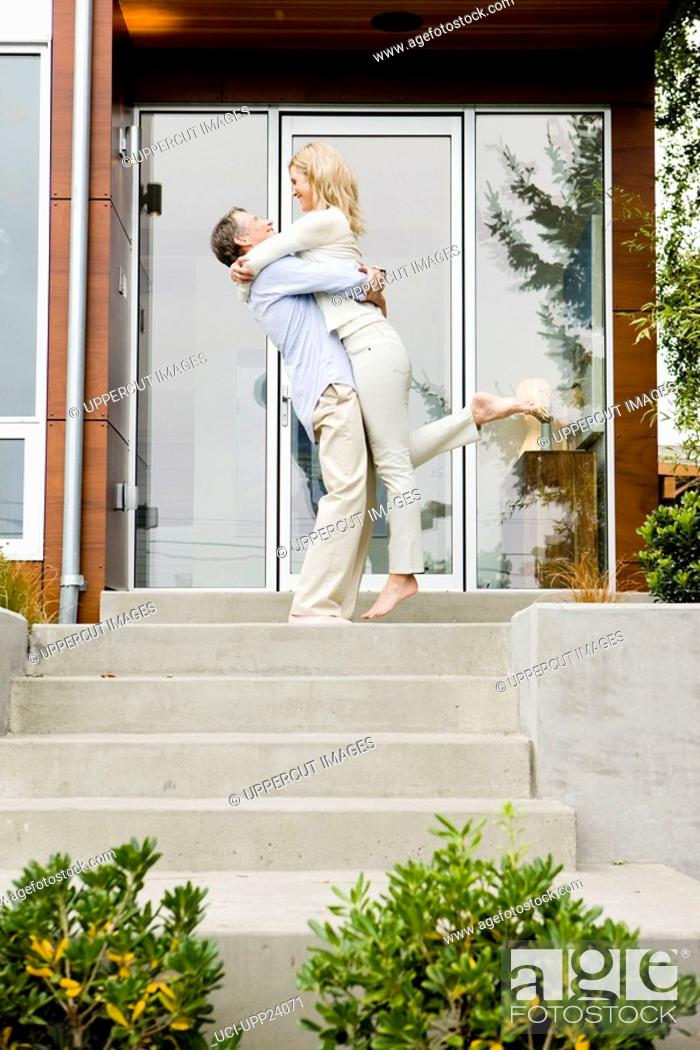 Stock Photo: Man hugging and lifting woman on front stoop.