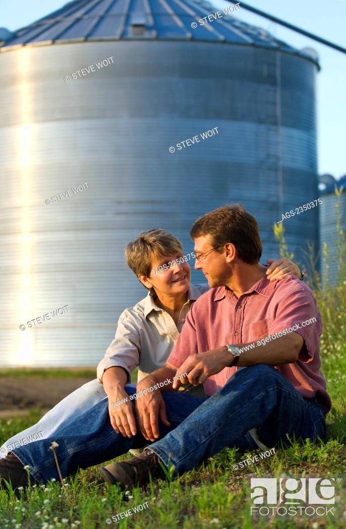 Stock Photo: Agriculture - Husband and wife farmers sit together while sharing some personal moments together, with grain bins in the background / Minnesota, USA.