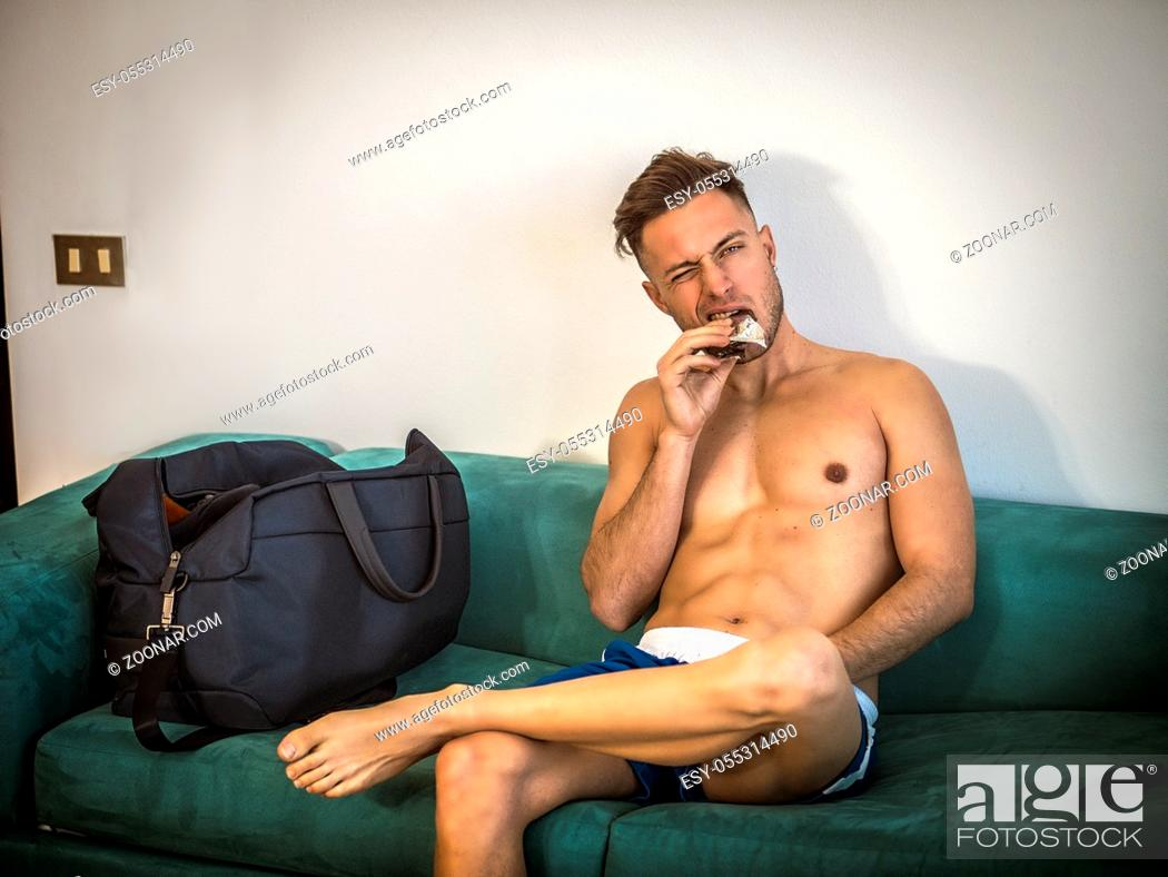 Photo de stock: Young muscular shirtless man eating protein bar indoor at home sitting on a couch.