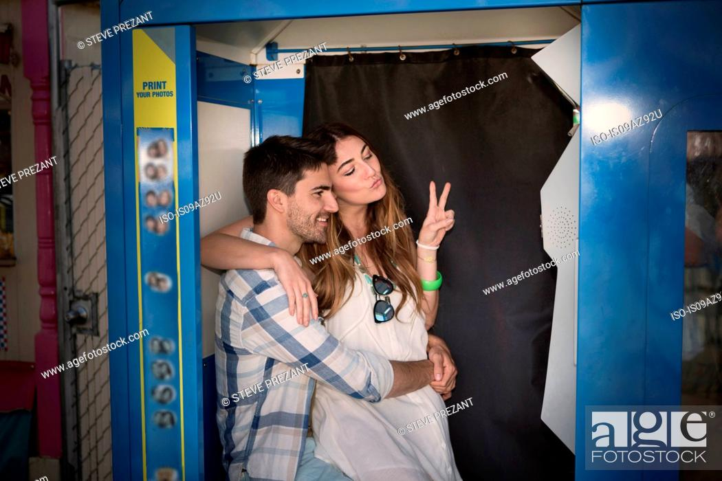 Stock Photo: Couple in photo booth doing peace sign, Coney island, Brooklyn, New York, USA.