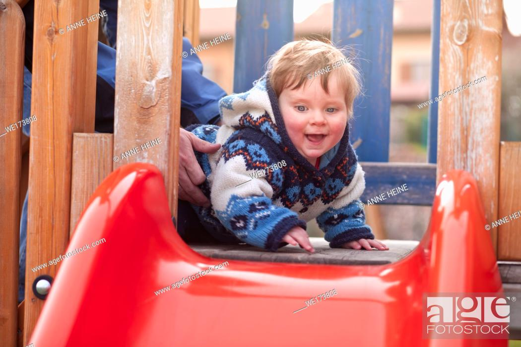 Stock Photo: Boy 9 months wants to slide a shute. Verona, Italy.