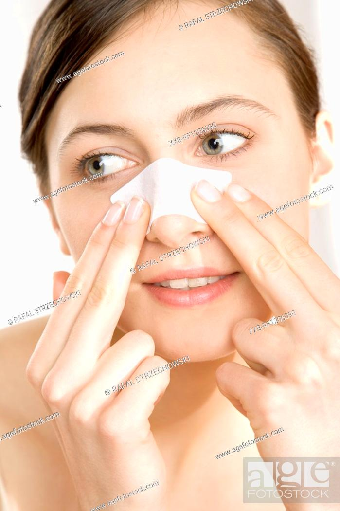 Stock Photo: young woman with cleansing strip on nose.