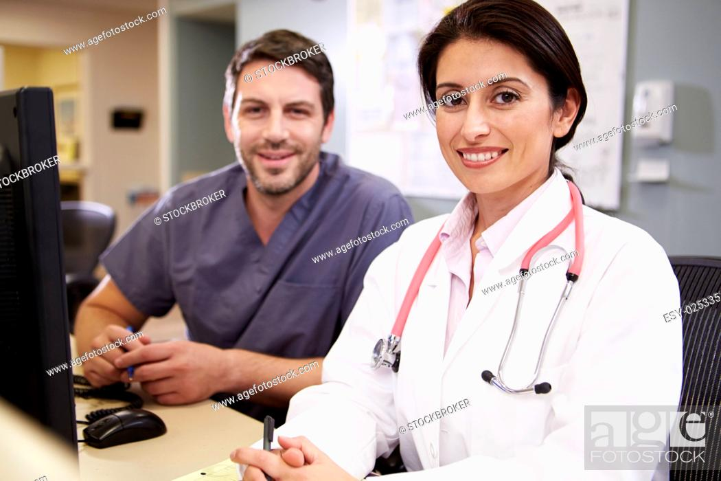 Stock Photo: Female Doctor With Male Nurse Working At Nurses Station.