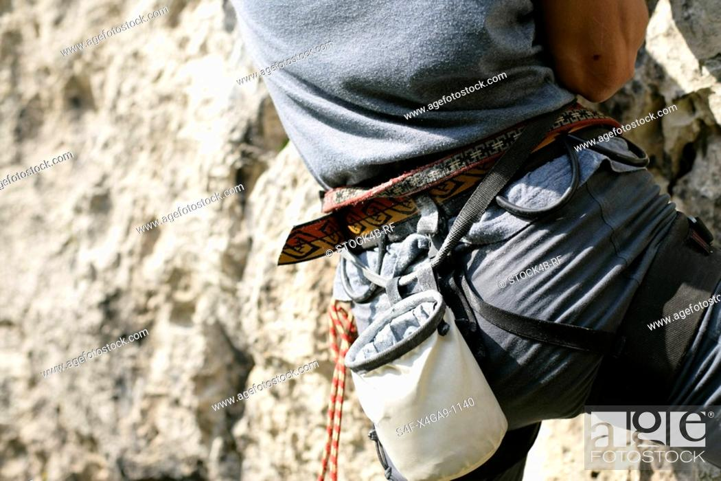 Stock Photo: Young man with a harness and a chalk bag is climbing up a rocky wall part of, close-up.