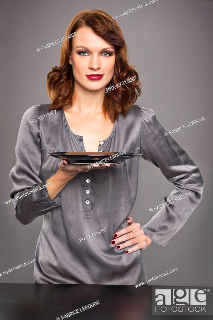 Stock Photo: Young woman holding plate.
