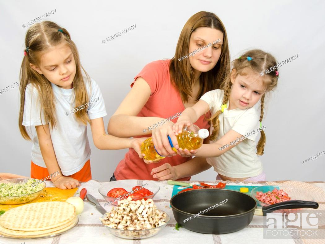 Stock Photo: Two little girls at the kitchen table with enthusiasm to help my mother to pour vegetable oil in a frying pan.