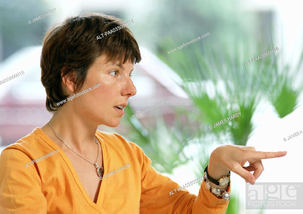 Stock Photo: Woman pointing finger, portrait.