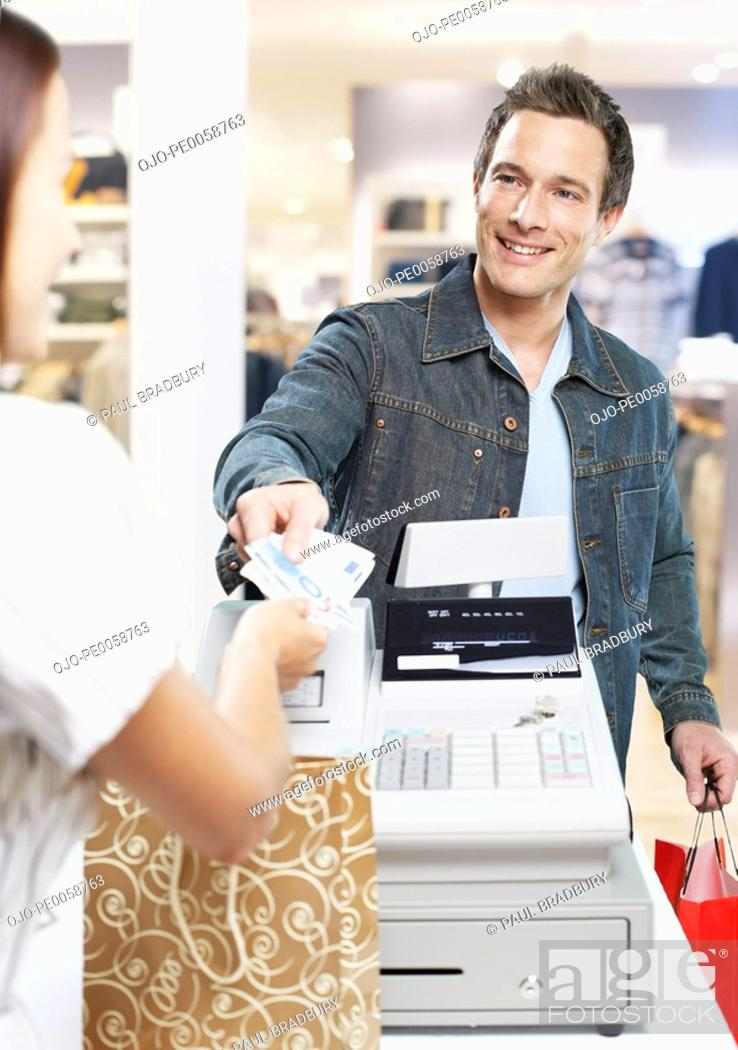 Stock Photo: Man paying for items at a cashier in store.