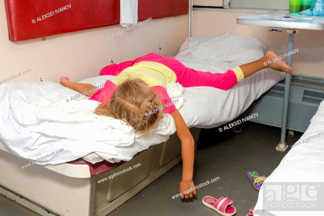 Stock Photo: Little girl on the train lies flat on the lower second-class place car dangling arm and a leg.