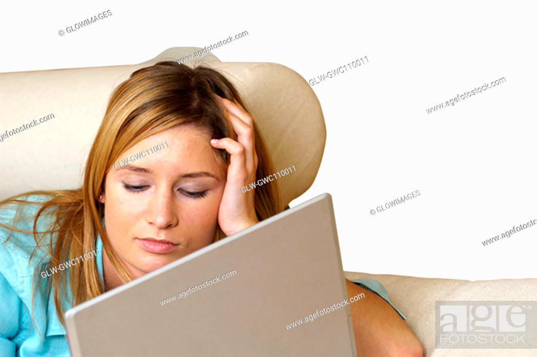 Stock Photo: Close-up of a businesswoman lying on a couch in front of a laptop.