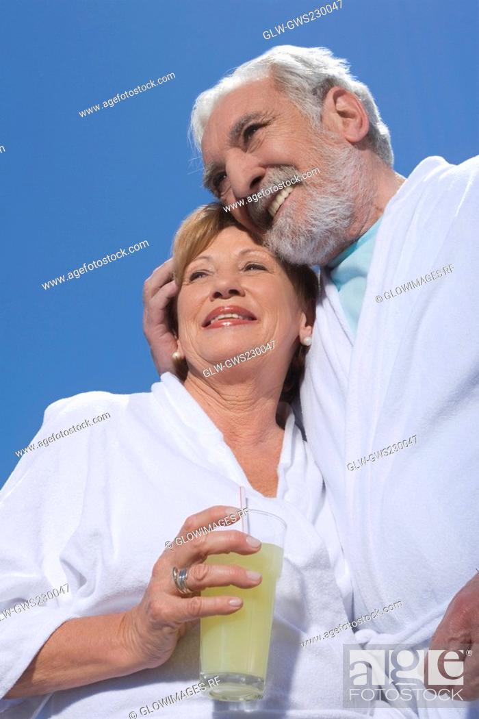 Stock Photo: Low angle view of a senior couple standing together with a glass of juice.