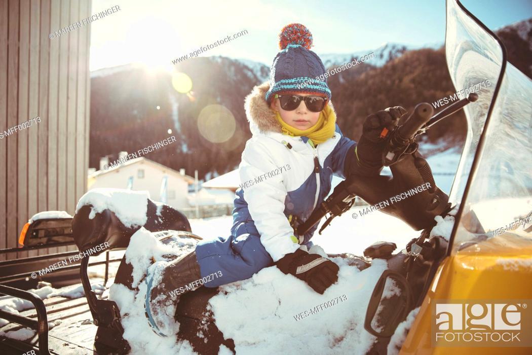 Imagen: Italy, Val Venosta, Slingia, boy with sunglasses sitting on a snowmobile.