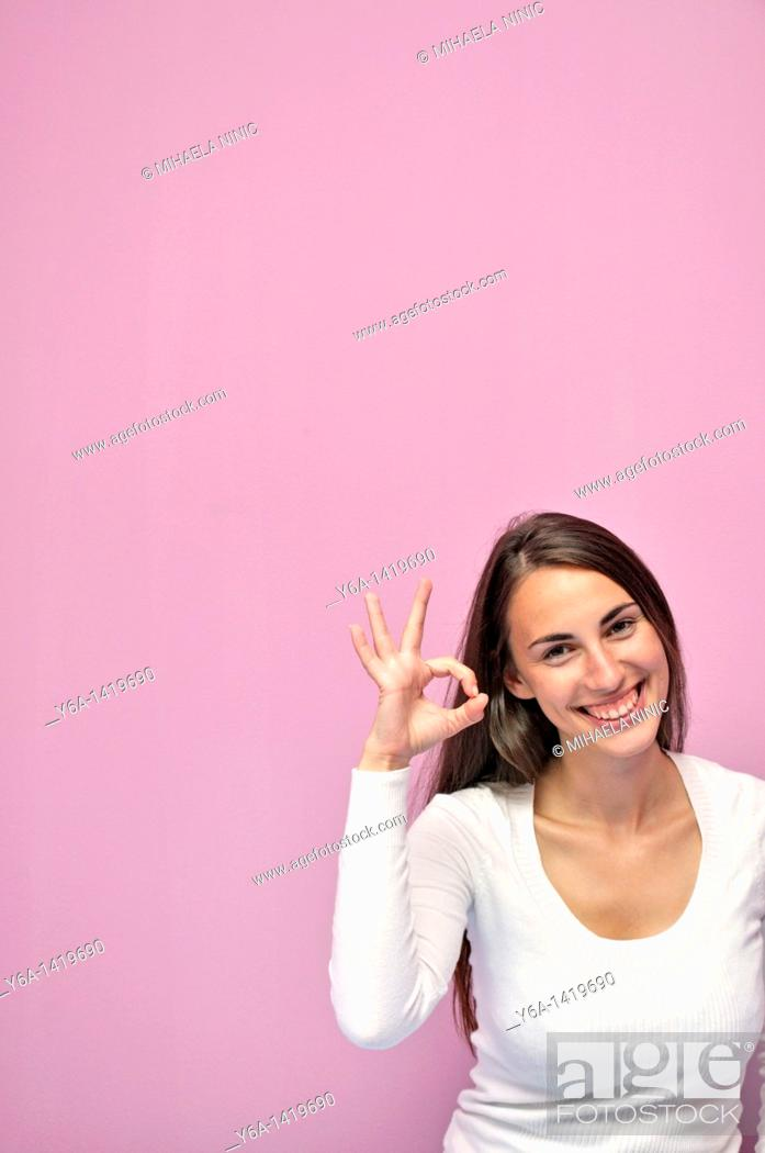 Stock Photo: Portrait of a smiling young businesswoman showing an ok sign.