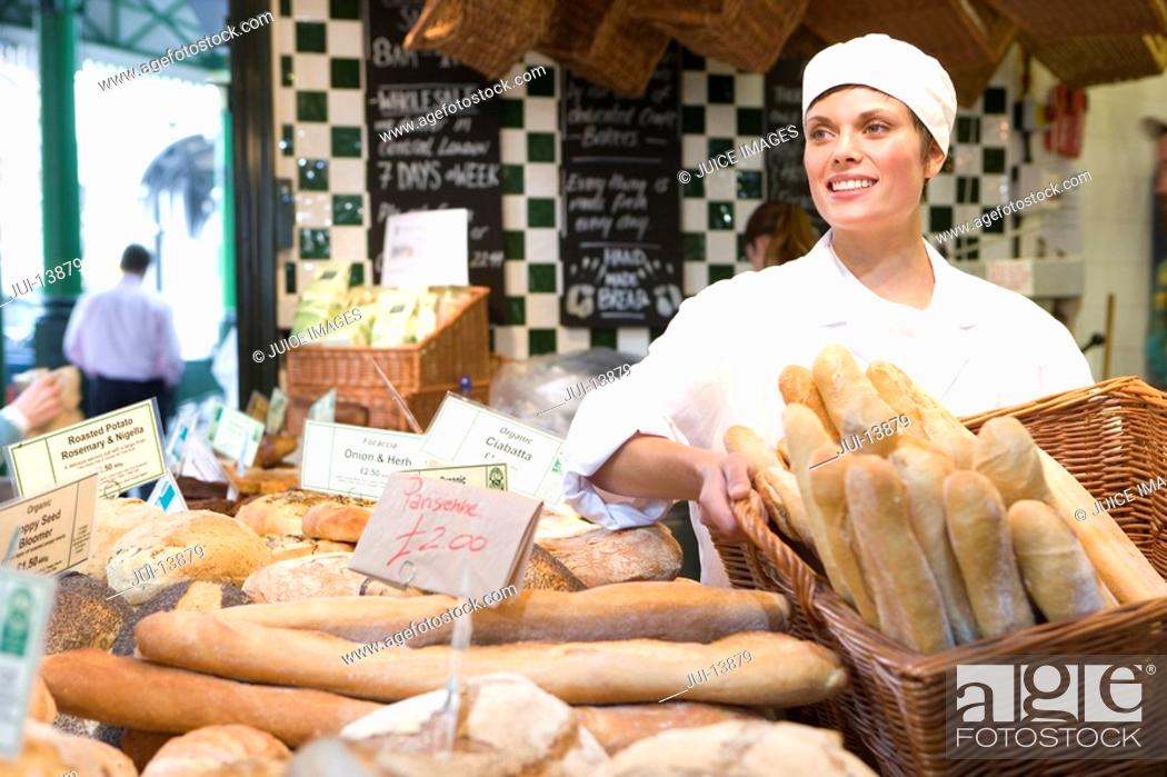 Stock Photo: Female baker with basket of baguettes in bakery, smiling.