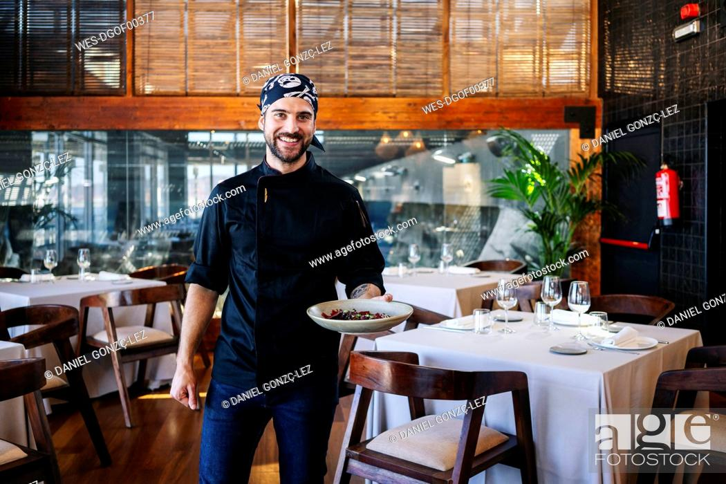Stock Photo: Portrait of smiling man serving a dish in restaurant.