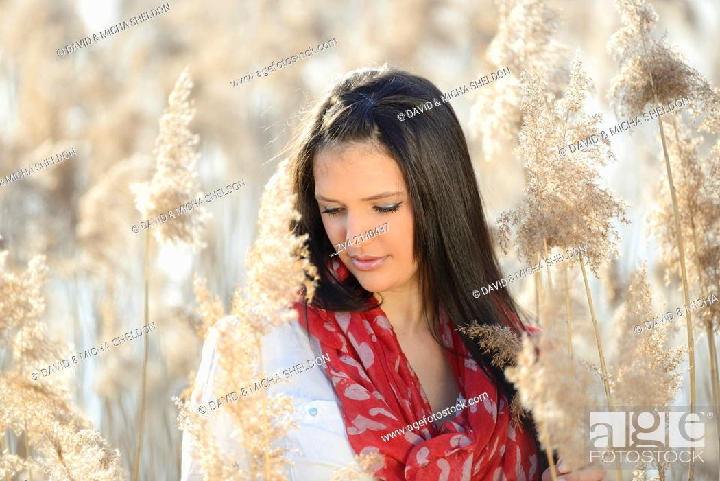 Stock Photo: Portrait of a good looking young woman in the reeds on a sunny day in early spring.