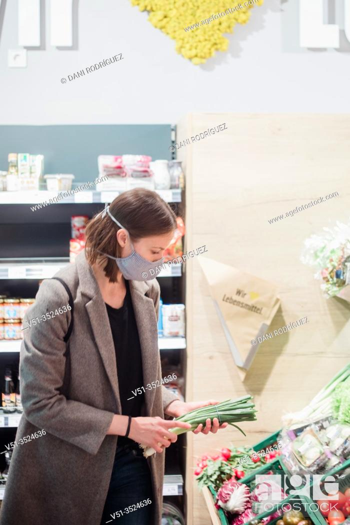 Stock Photo: Woman in mask buying vegetables at grocery store.