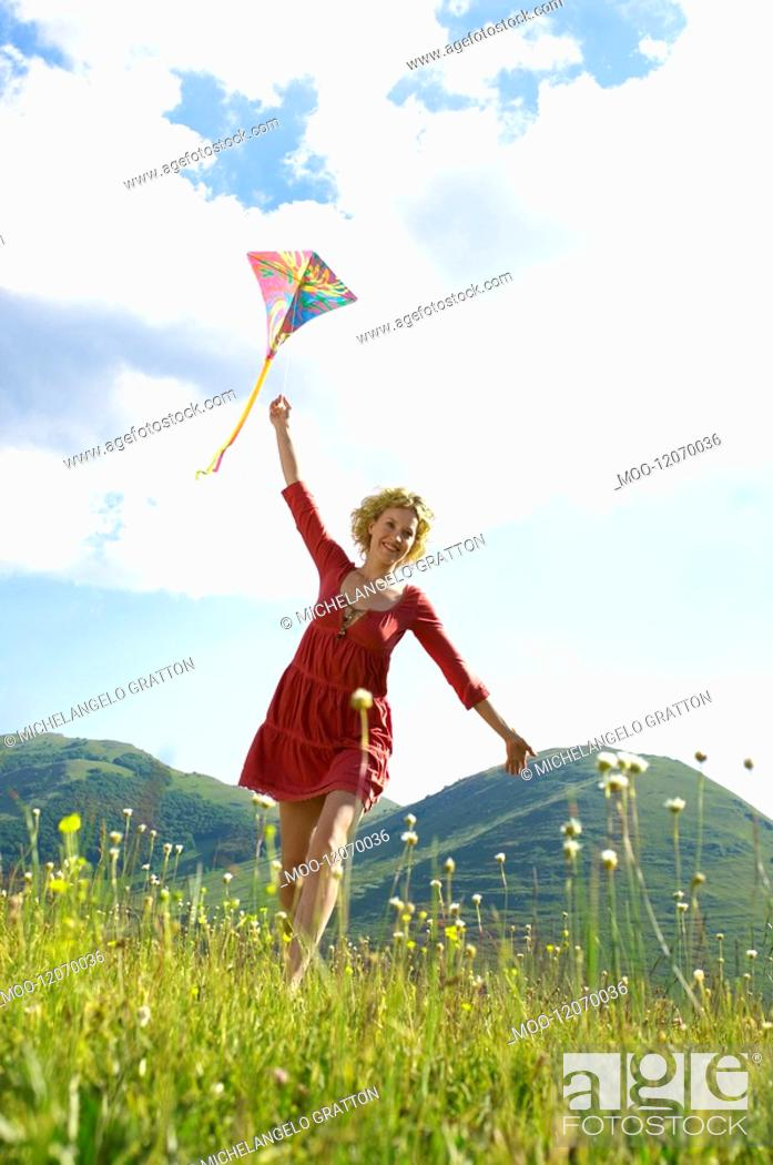 Stock Photo: Woman Flying Kite in mountain field front view.