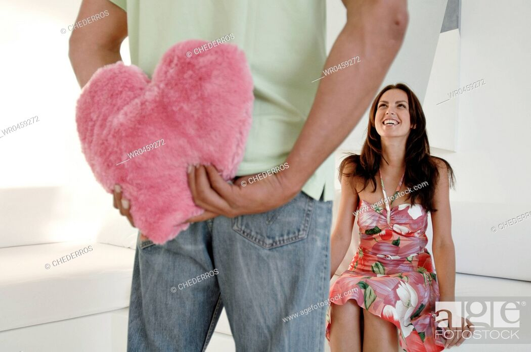Stock Photo: Mid section view of a man hiding a stuffed pink heart behind his back with a young woman sitting on a couch.