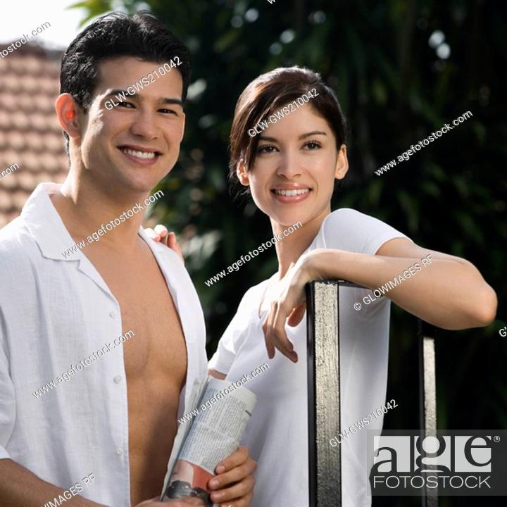 Stock Photo: Young couple standing and smiling together.