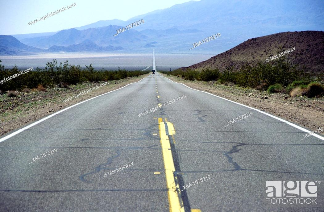 Stock Photo: Yellow lines in straight road crossing Mojave desert between Baker and Death Valley, California, USA.