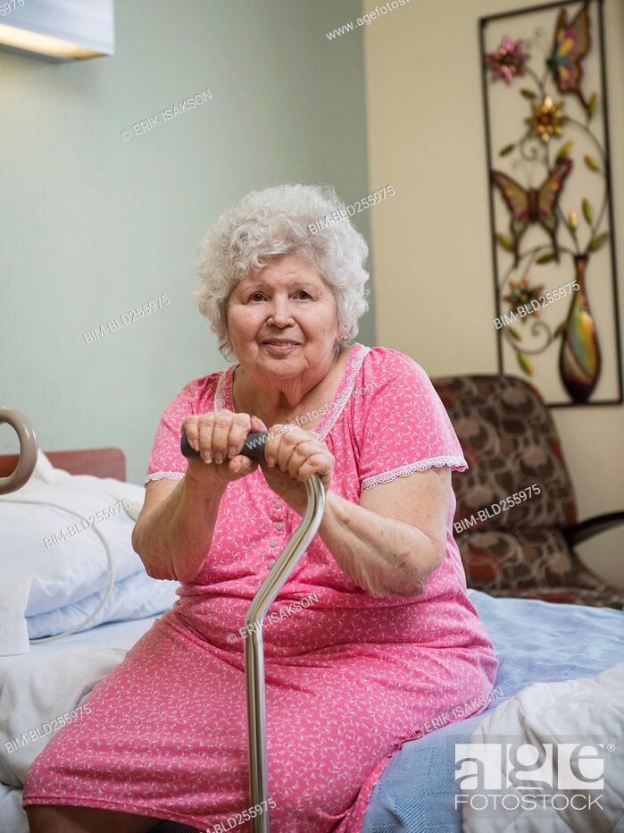 Stock Photo: Smiling Caucasian woman sitting on bed leaning on cane.