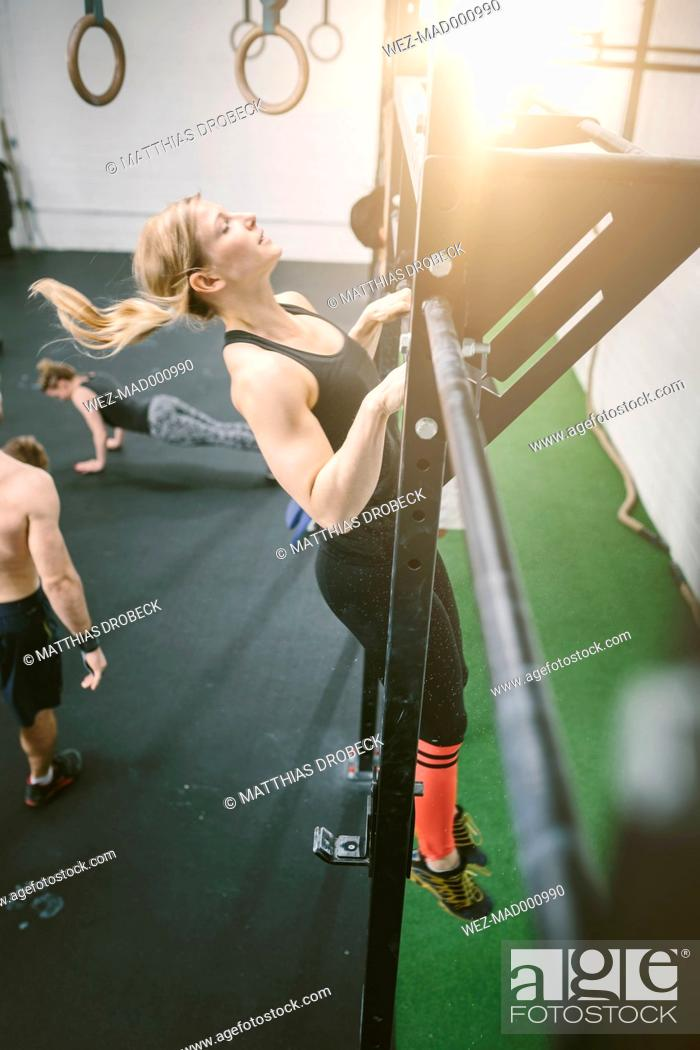 Stock Photo: Woman in gym doing chin ups.