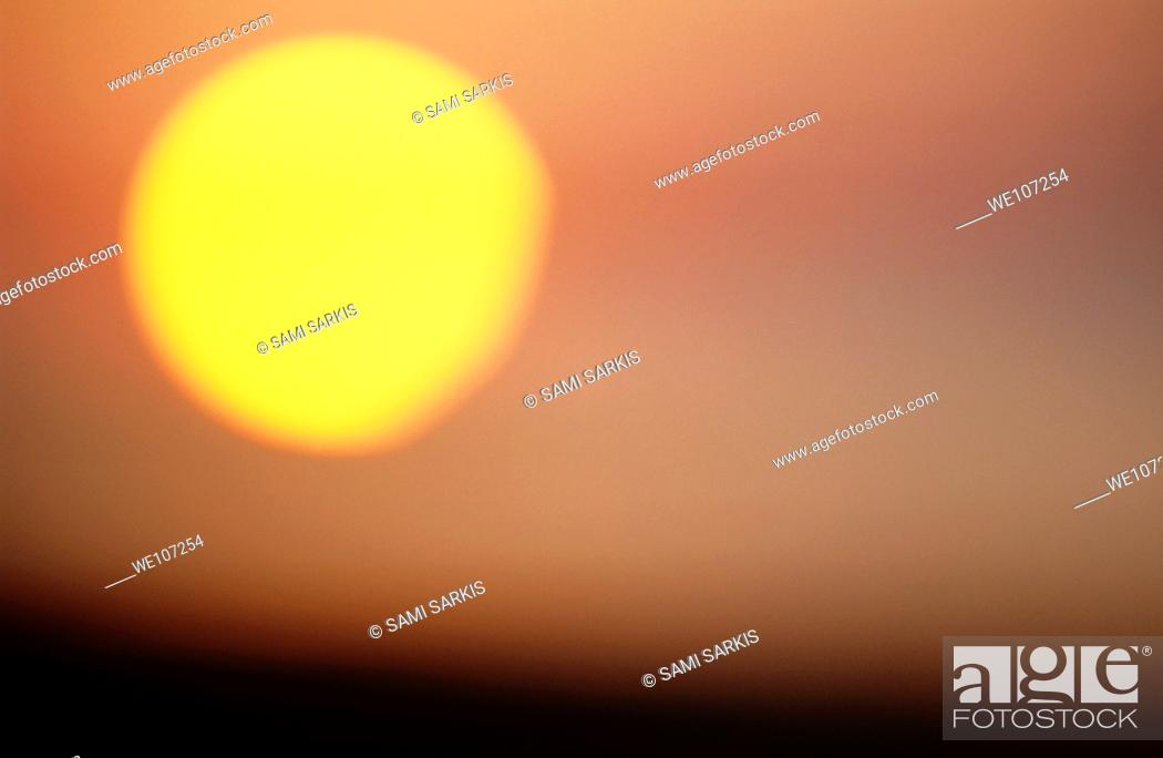 Stock Photo: Blurred solar disc at sunrise creating a dramatic sky.