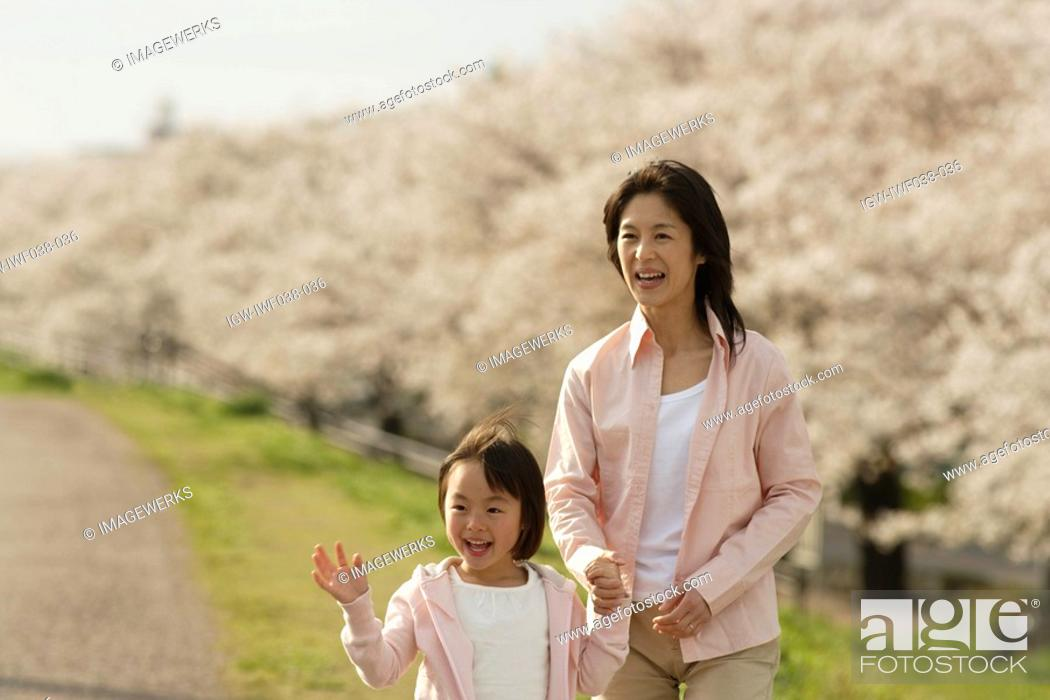 Stock Photo: View of a mother and daughter holding hands.