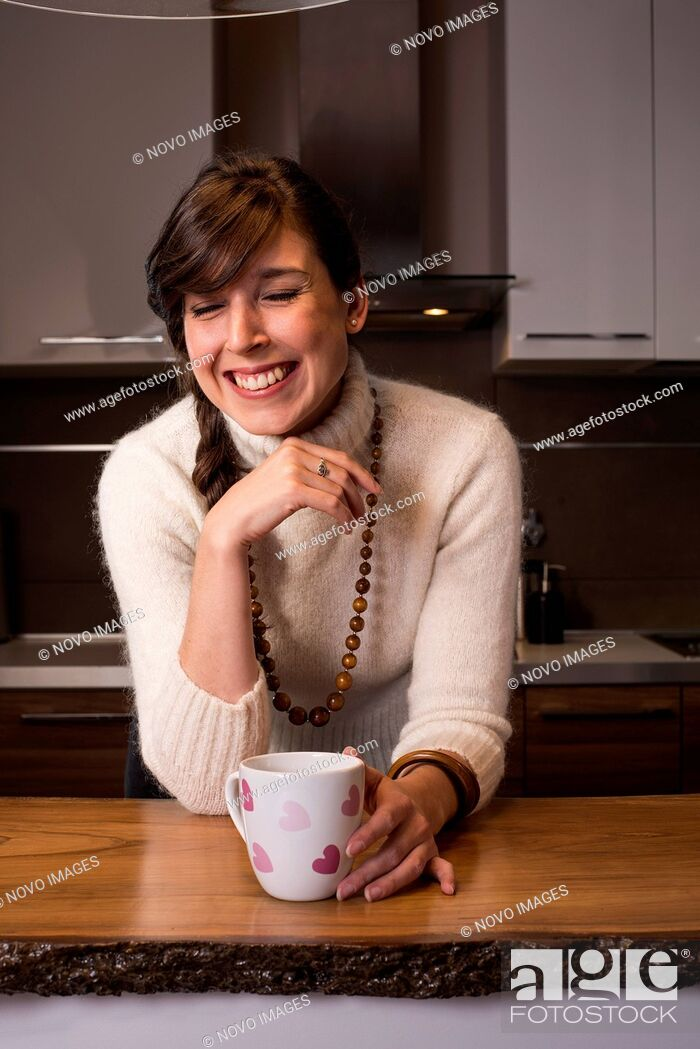 Imagen: Laughing Woman with Cup with Pink Hearts in Kitchen.