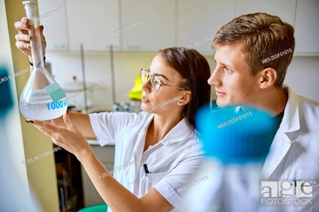 Stock Photo: Young man and woman looking at liquid in flask in laboratory.