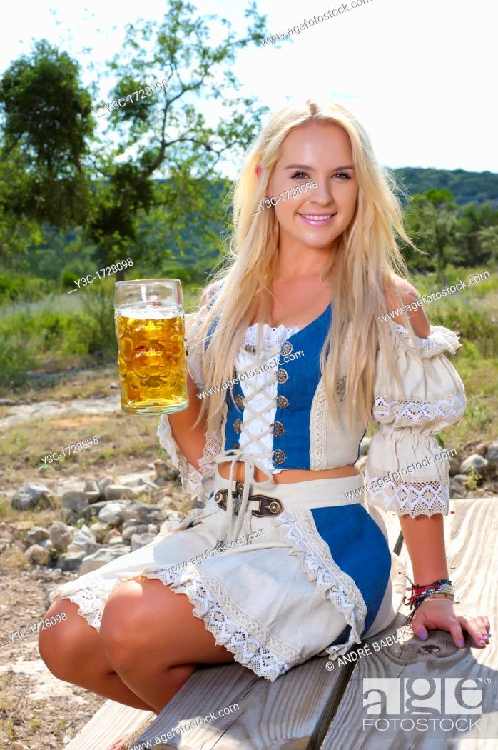 Stock Photo: Blond German woman in traditional dirndl dress with beer glass.
