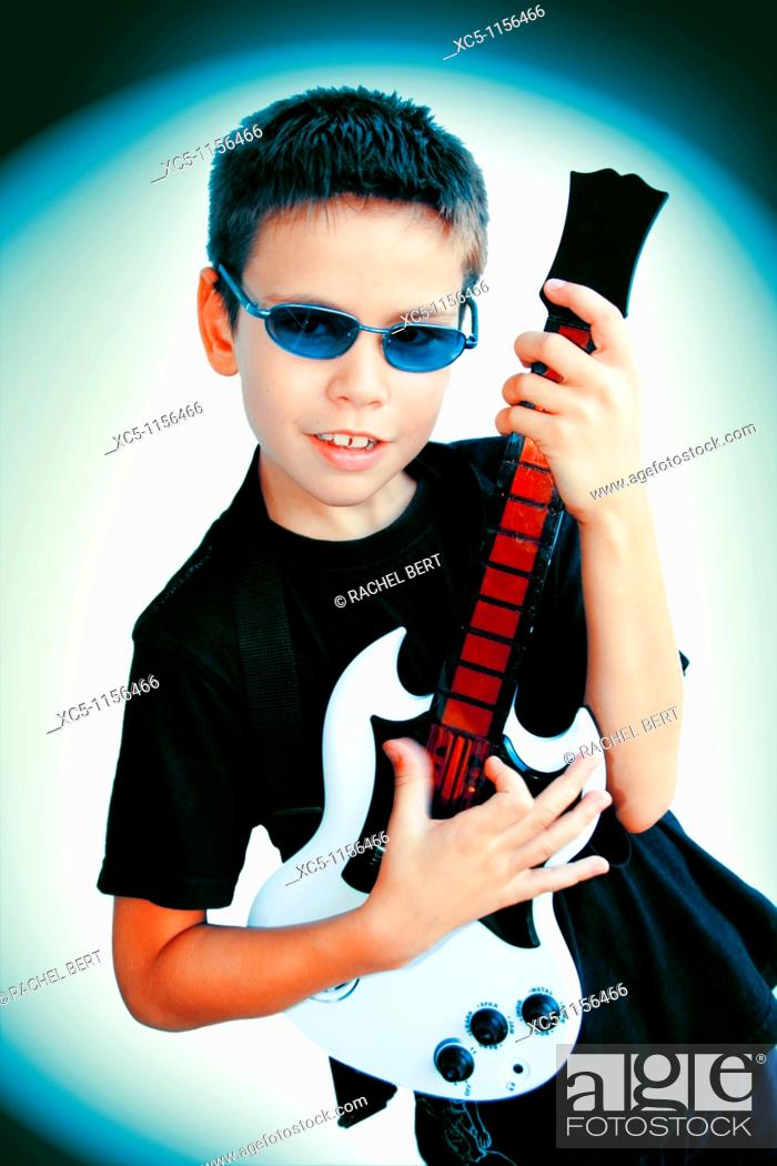 Stock Photo: 9 years old boy playing guitar.