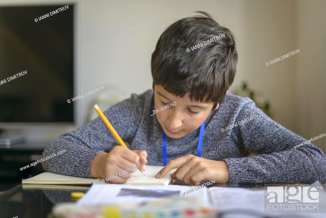 Stock Photo: Schoolboy working on homework, Surrey, UK.