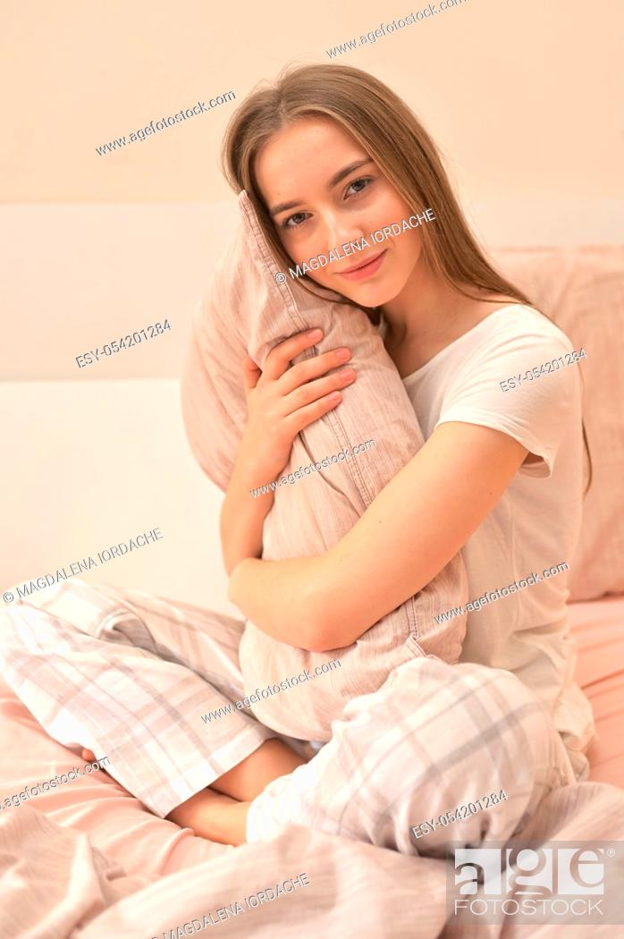 Stock Photo: Morning Young Woman With Pillow On Bed In Bedroom.