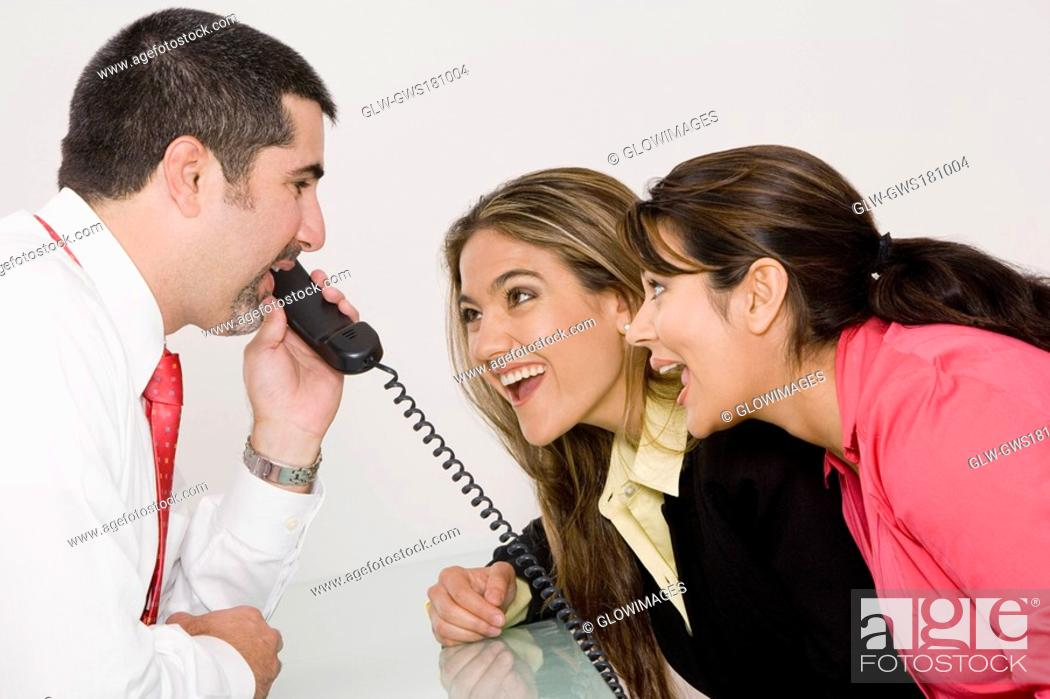 Stock Photo: Side profile of a businessman talking on the telephone with two businesswomen looking at him and smiling.