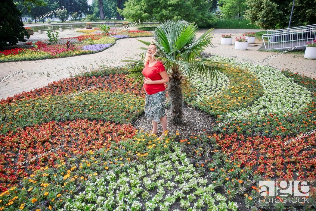 Stock Photo: Happy pregnant woman standing amidst blooming flowers in park.
