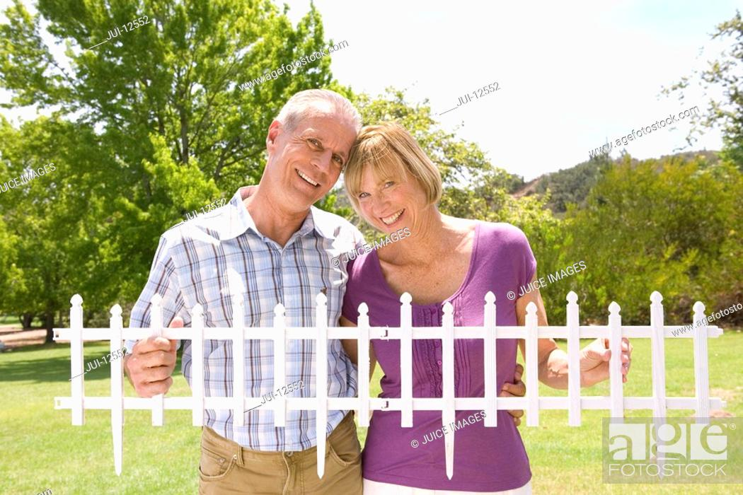 Stock Photo: Mature couple holding small picket fence outdoors, smiling, portrait.