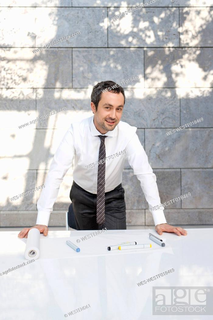 Stock Photo: Germany, Leipzig, Businessman with pen and marker on desk, portrait.