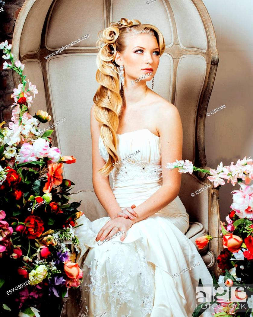 Photo de stock: beauty emotional blond bride in luxury interior dreaming, crazy complicate hairstyle, many flowers.