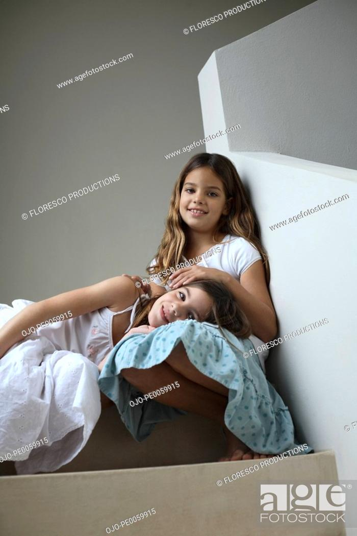 Stock Photo: Two young girls on staircase indoors relaxing.