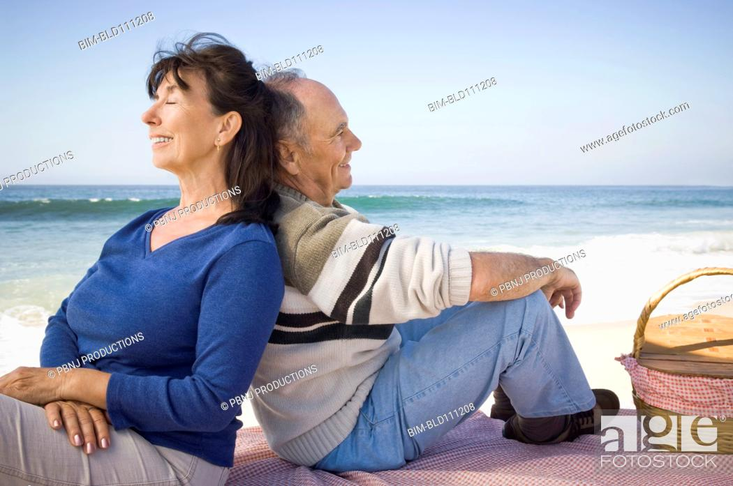 Stock Photo: Couple relaxing at picnic on beach.