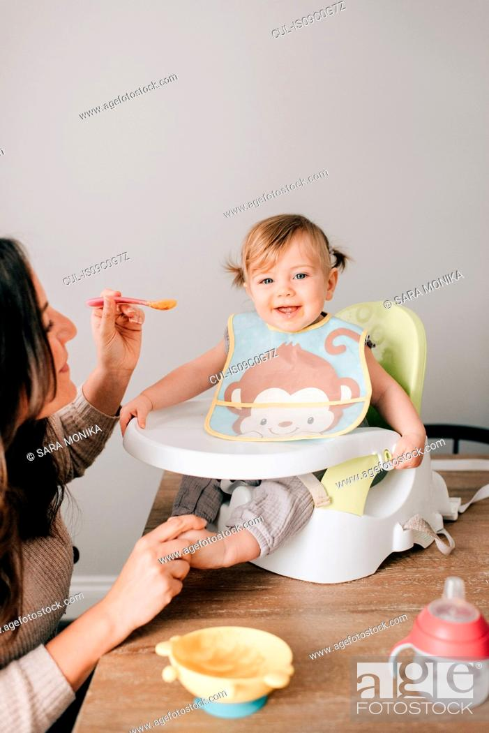 Stock Photo: Mother feeding baby daughter in child seat, portrait.