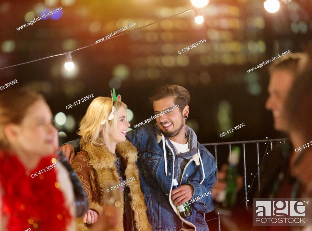 Stock Photo: Young couple drinking and enjoying nighttime rooftop party.