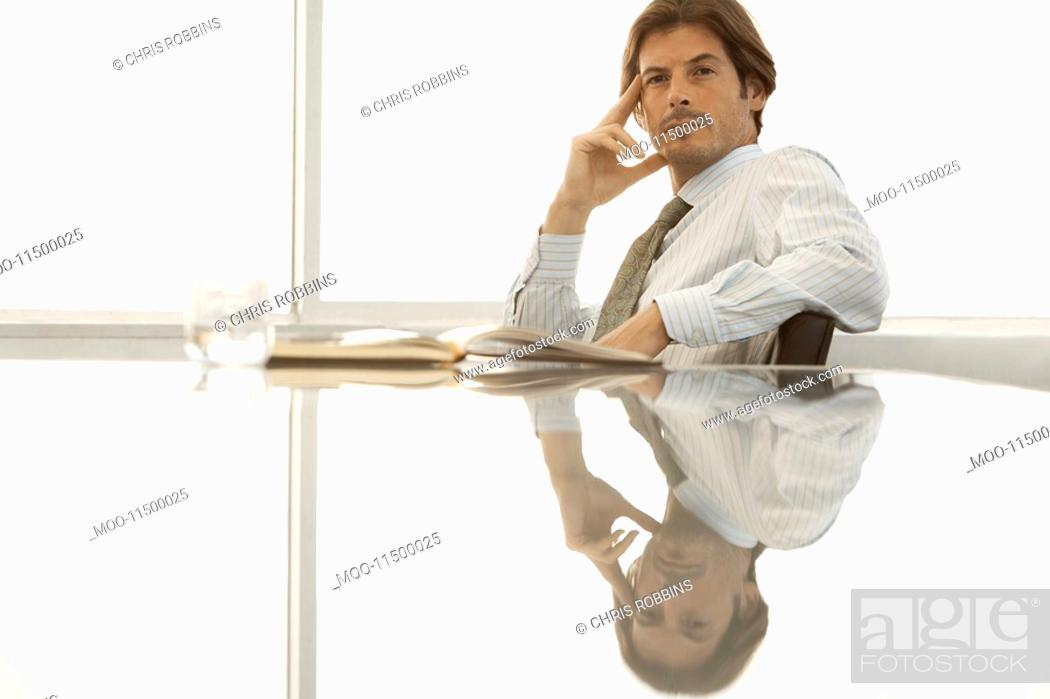 Stock Photo: Serious businessman sitting at conference table.