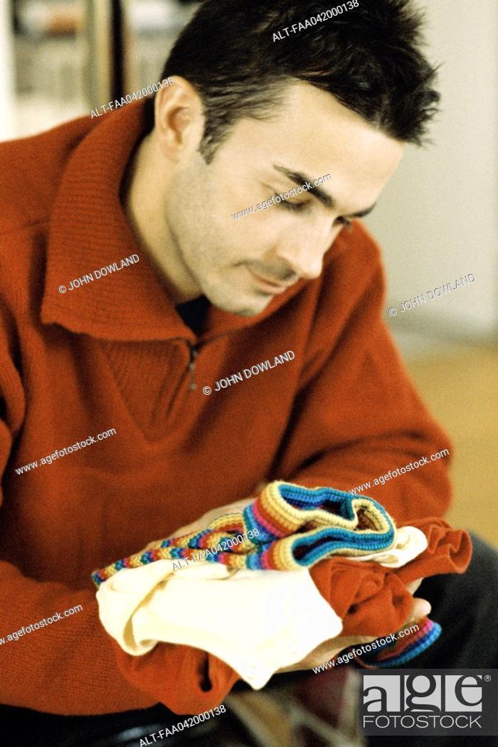 Stock Photo: Man looking at baby clothes, close-up.