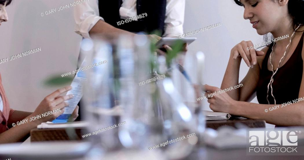 Stock Photo: Waiter serving diners in restaurant, using digital tablet, mid section.