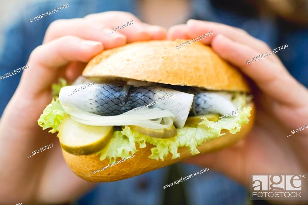 Stock Photo: Hands holding a fish roll.