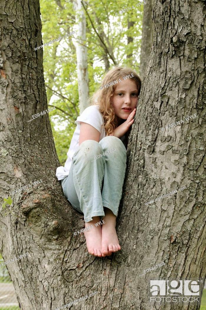 Imagen: Preteen girl with wavy gold-brown hair and freckles, sitting in tree, in faded jeans and white short-sleeved top, knees close to body and leaning on hand.